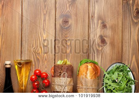 Two sandwiches with salad, ham, cheese and tomatoes, salad and spices on wooden table. Top view with copy space