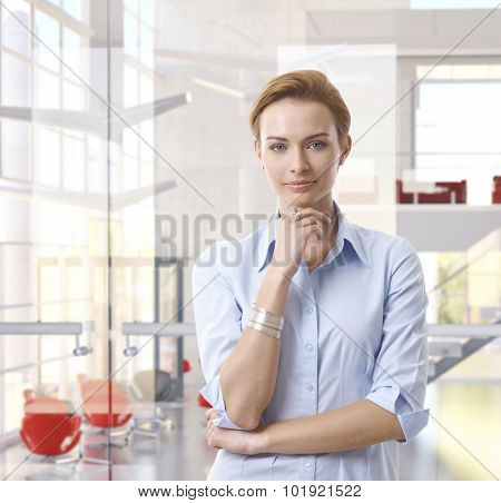 Casual attractive caucasian businesswoman standing at classy bright business office, looking at camera, hand under chin, copyspace.