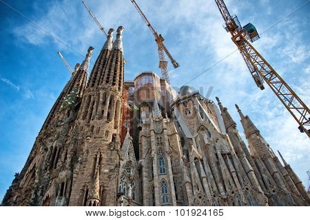 BARCELONA, SPAIN - MAY 02: Exterior view of the ornate spires of the Sagrada Familia with cranes, a historic landmark Roman Catholic Church still under construction. May 02, 2015 in Barcelona Spain