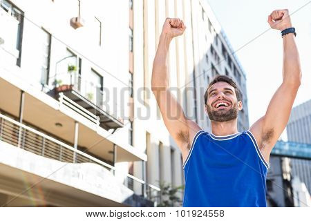 Happy handsome athlete triumphing in the city