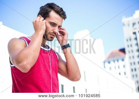 Serious handsome athlete putting on his earphones on a sunny day