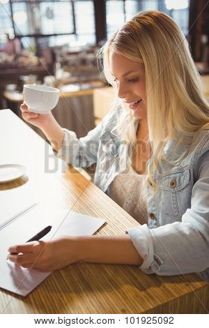 Smiling blonde drinking coffee and writing on sheet of paper at coffee shop
