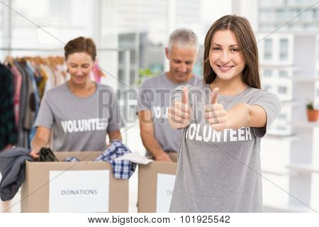 Portrait of smiling female volunteer doing thumbs up in the office