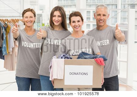 Portrait of smiling volunteers with donation box in the office