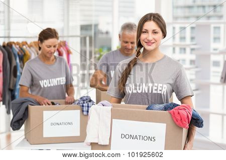 Portrait of smiling female volunteer carrying donation box in the office