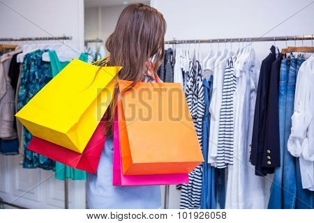 Woman holding shopping bags over shoulder in fashion boutique