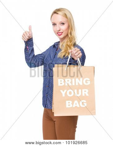 Woman with shopping bag and thumb up for showing phrase bring your bag