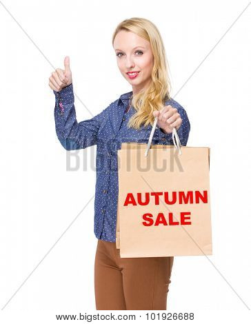 Woman with shopping bag and thumb up for showing phrase autumn sale