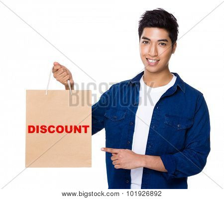 Man finger point to shopping bag for showing a word discount