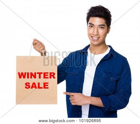 Man finger point to shopping bag for showing phrase of winter sale