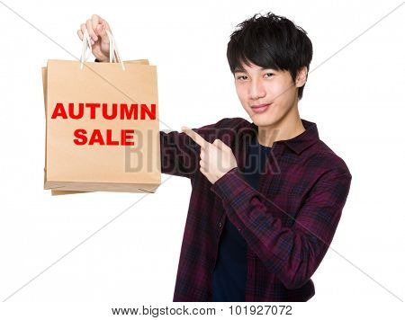 Happy young shopper with finger point to paper bag for showing phrase of autumn sale