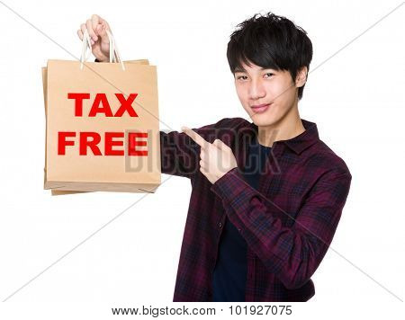 Happy young shopper with finger point to paper bag for showing phrase of tax free