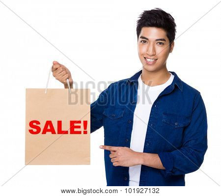 Man finger point to shopping bag for showing a word sale!