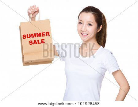 Woman hold with shopping bag and showing phrase of summer sale