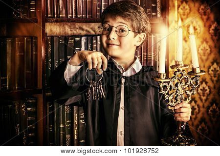 Emotional boy stands with a bunch of old keys and candles in the library with many old books. Fairy tales. Vintage style.