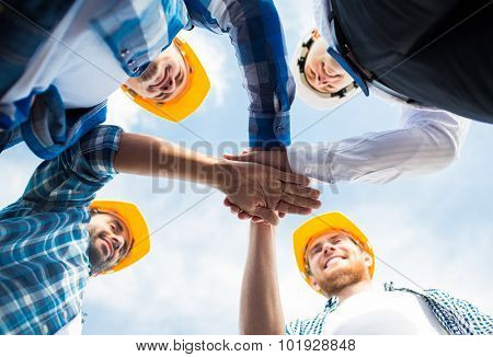 business, building, partnership, gesture and people concept - close up of smiling builders in hardhats with hands on top outdoors