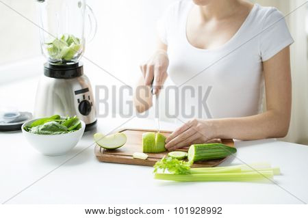 healthy eating, cooking, vegetarian food, dieting and people concept - close up of young woman with blender chopping green vegetables for detox shake or smoothie at home