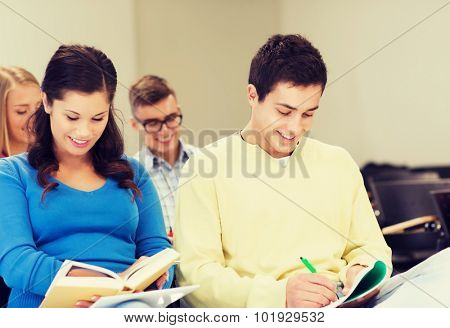 education, high school, teamwork and people concept - group of smiling students with notebooks and book sitting in lecture hall and writing