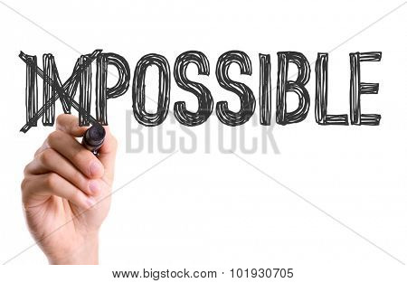 Hand with marker writing the word Impossible/Possible