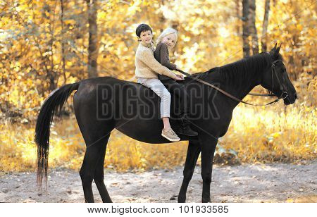Two Children Boy And Girl Riding On Horse In Autumn Forest