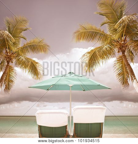 lounge chairs and umbrella at a tropical paradise beach