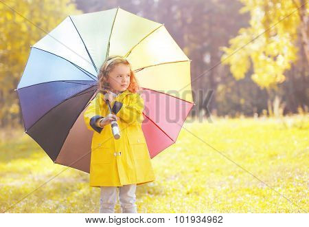 Cute Little Girl Child In Yellow Jacket With Colorful Umbrella Over Autumn Park Background