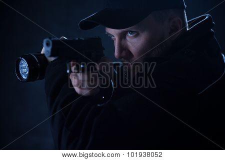 Policeman Holding Gun And Flashlight