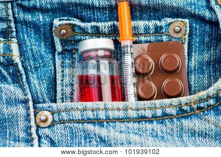 Closed up medicine and injection syringe in jeans bag