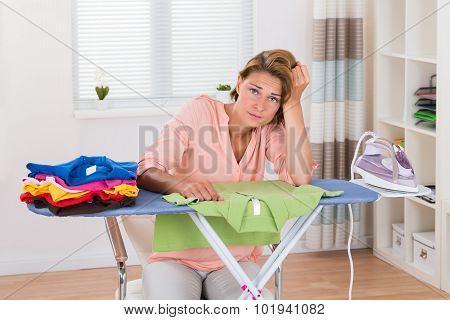 Bored Woman With Electric Iron And Clothes