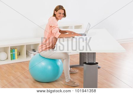 Woman Sitting On Fitness Ball Using Laptop