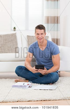 Man Calculating Budget With Calculator