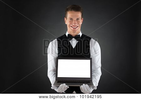 Happy Waiter Showing Laptop