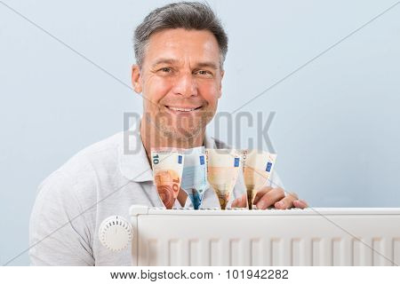 Man Placing Euro Notes On Radiator