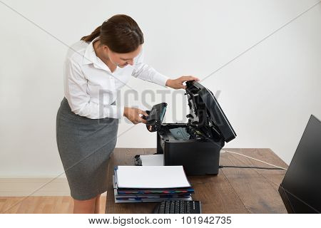 Businesswoman Putting Laser Toner Cartridge In Printer