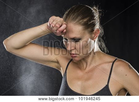 Pensive Sporty Woman with Hand on Forehead