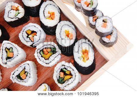 Maki Rolls and California rolls made of fresh raw Salmon, Tuna and Eel with Cream Cheese and Avocado . Isolated over white background . on wooden plate with live crab . Maki Sushi and Nigiri