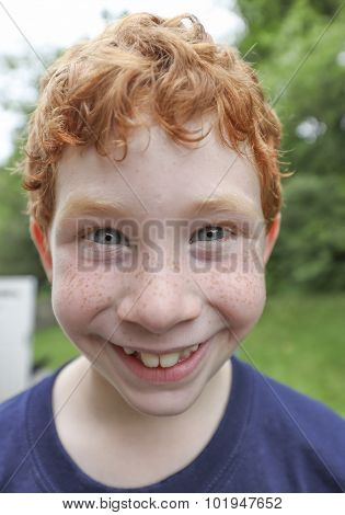 Happy redheaded boy close up smiling at camera