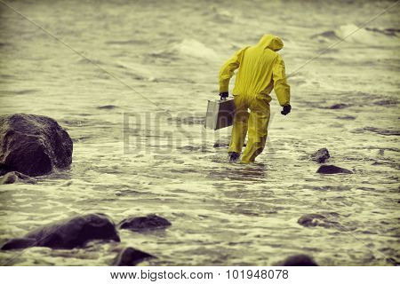 technician  in protective suit with silver case  walking in water at rocky beach - back view