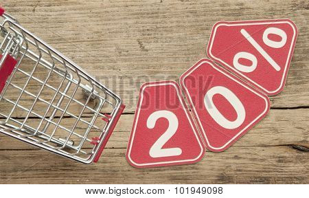 discount 20%, shopping cart on wood background