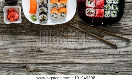 assorted sushi on plates and a text spase on wooden background