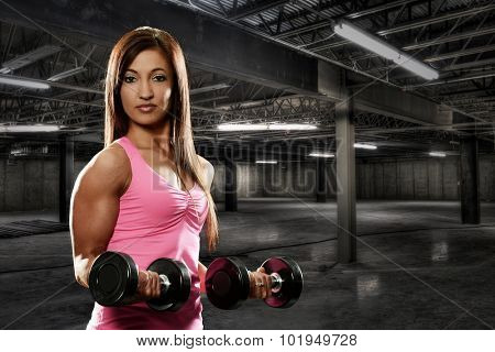 Young Woman working out  inside a dark building