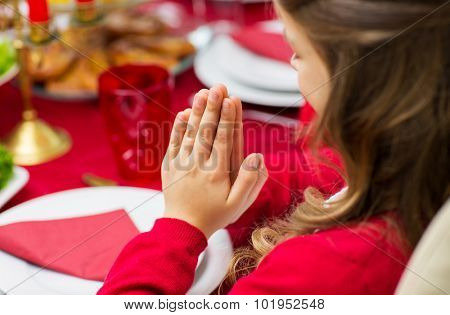 family, holiday, religion, tradition and people concept - close up of girl praying at christmas dinner at home