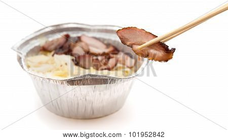 Chopsticks Catching A Piece Of Barbeque Pork With A Fast Food Bowl At Background On White