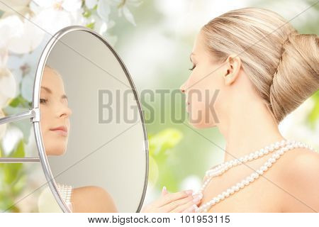 beauty, luxury, people, holidays and jewelry concept - beautiful woman with sea pearls beads or necklace looking to mirror over cherry blossom background