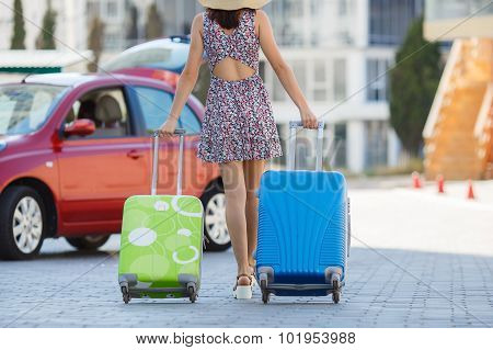 Woman traveling with suitcases, walking on the road