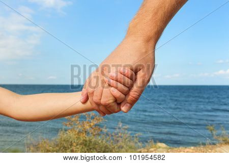 Man holds hand of child on background of sea and sky Concept of love, care, trust in family.