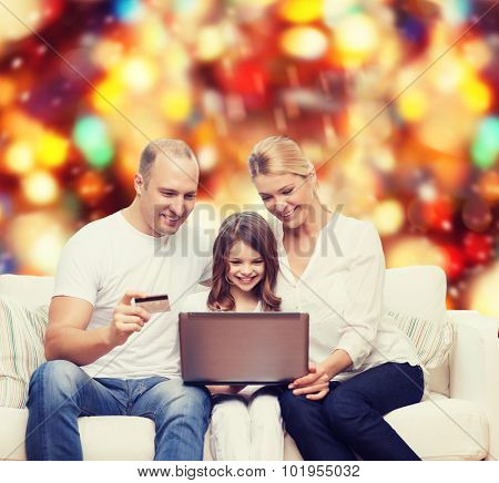 family, holidays, shopping, technology and people concept - happy family with laptop computer and credit card over red lights background