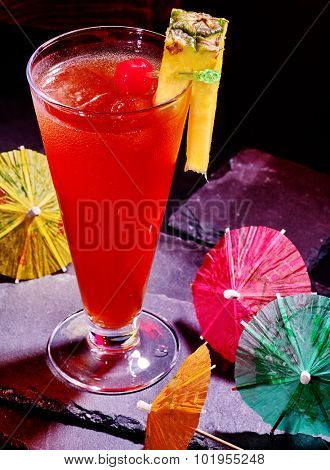 Pineapple cocktail with cherry and group umbrella in highball glass .