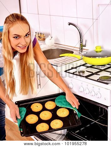 Young woman bake tasty cookies at home kitchen.