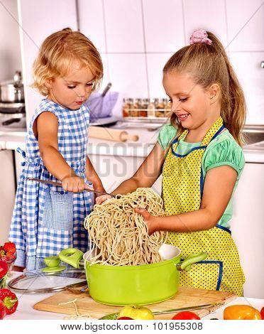 Children  eating spaghetti at kitchen.